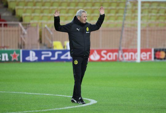 Lucien Favre steht im schwarzen Trainingsanzug von Borussia Dortmund auf dem Platz