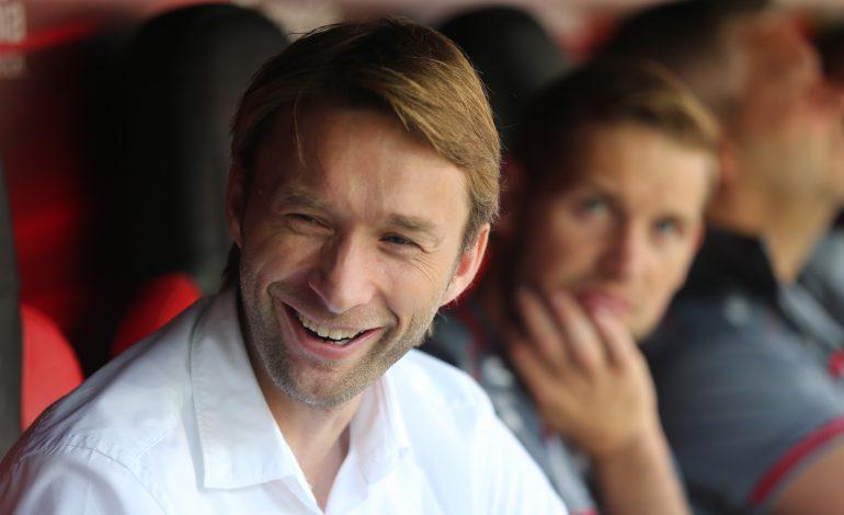 Simon Rolfes hat ein weißes Hemd an und redet lächelnd mit seinem Nebenmann