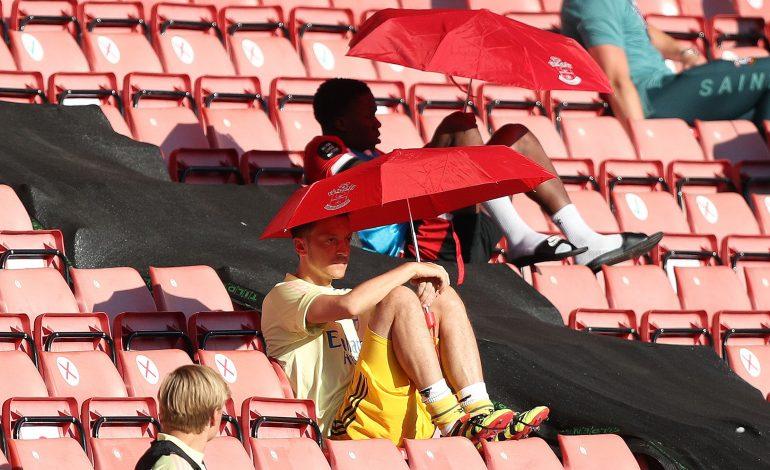 Mesut Özil versteckt sich unter einem Sonnenschirm auf der Tribüne im Spiel gegen Southampton
