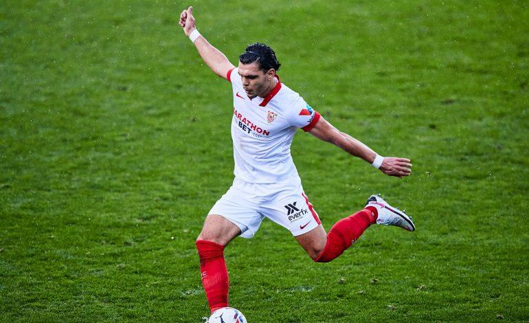 Ein schwarzhaariger Fussballspieler im weißen Trikot schießt einen Ball